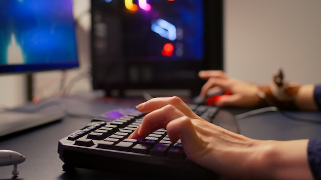 Close-up of gamer using rgb keyboard and mouse for online competition