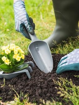 Close-up of gardener digging soil with shovel