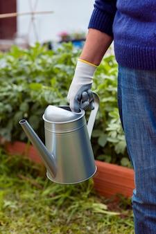 Крупный план садовника, держа спринклер в саду