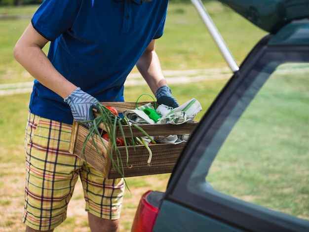 Close-up of gardener holding vegetable crate near the car