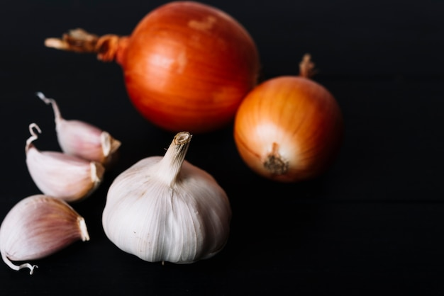 Close-up of garlic bulb and onions on black background