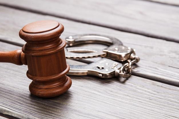Крупным планом молоток и наручники. деревянный молоток и металлические наручники на столе.
