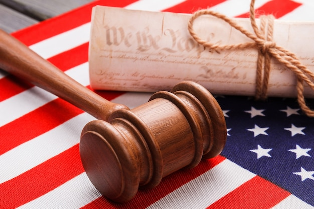 Close-up gavel with scroll and usa flag. independence declaration concept.