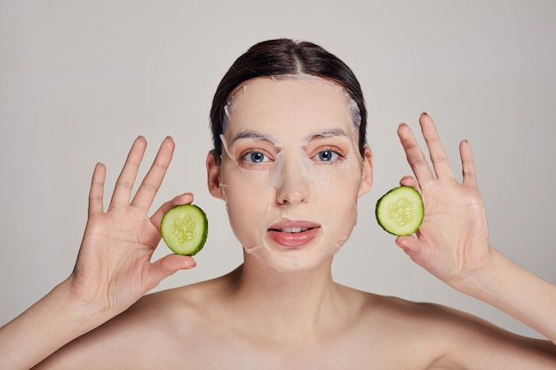 Close up gentle sophisticated calm woman in a moisturizing mask with a fresh cucumber on the face in the serious with open eyes and hands holds a cucumbers in both hands near face