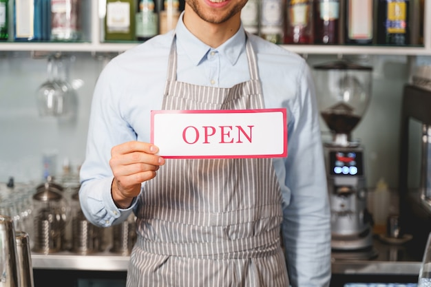Close up of gentleman demonstrating signboard with word open and inviting to visit his cafe