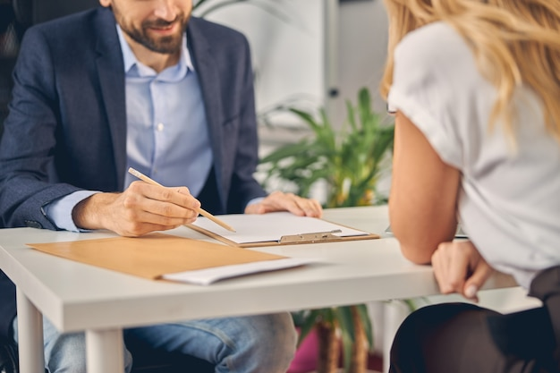 Close up of gentleman holding pencil and smiling while sitting across the table from female colleague