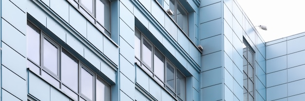 Close-up of geometric facade with plain lines and corners. aluminum panels on city building. texture of white grey and silver colours. urban geometry concept