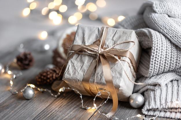 Primo piano di una confezione regalo, dettagli di una decorazione natalizia festiva ed elementi a maglia su uno sfondo sfocato con bokeh.