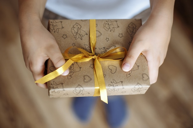 Close up of a gift box in the hands of a child
