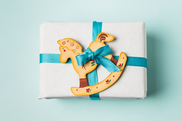 Close-up of a gift box and rocking horse toy tied with blue ribbon on background