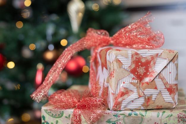 美しいモミの木の背景に赤い弓でクラフト紙で覆われた新年とクリスマス休暇のギフトプレゼントボックスを閉じます