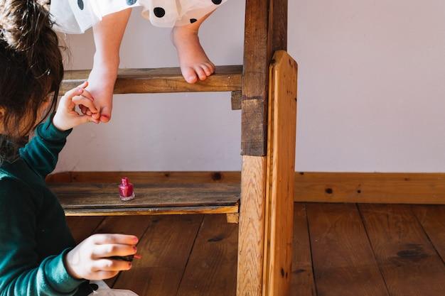 Close-up of a girl applying nail polish on her sister's toe nail at home