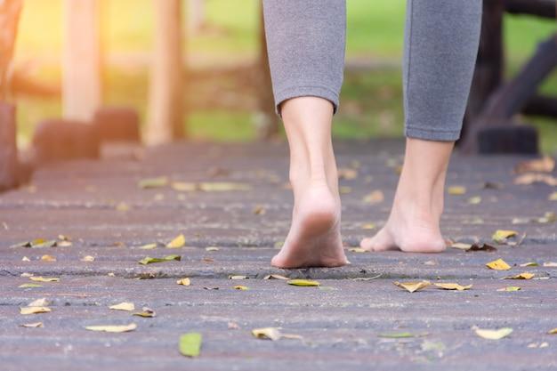 Close up  of girl barefoot walking on walk way in garden