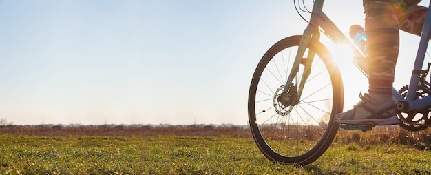 Close-up of a girl on a bicycle riding on green grass