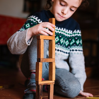 Close-up of a girl building wooden blocks