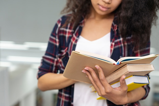 Close-up girl carrying stack of books while reading