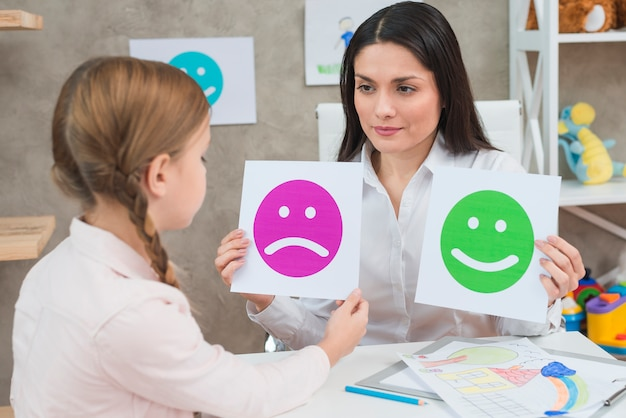Close-up of a girl choosing sad face emoticons paper held by smiling young psychologist
