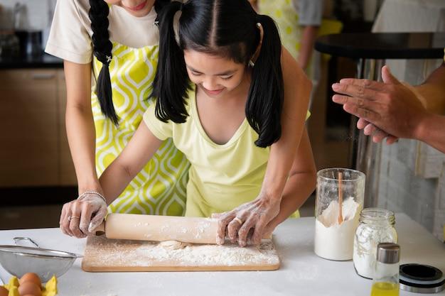Chiuda sulla ragazza che cucina a casa