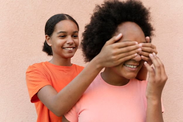 Close up girl covering friend's eyes