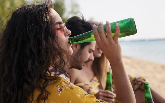 Chiuda in su della ragazza che beve birra con gli amici sulla spiaggia.