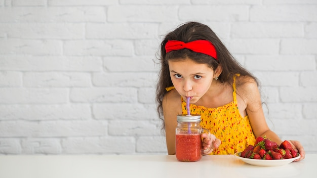 Close-up of a girl drinking strawberry smoothies jar
