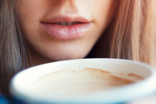 A close-up of a girl drinks her lips with a cup of coffee.