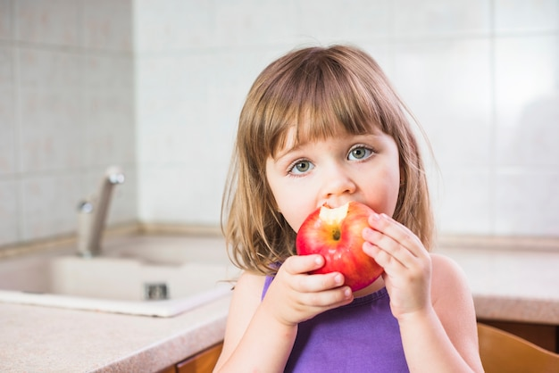 Close-up of a girl eating healthy red apple