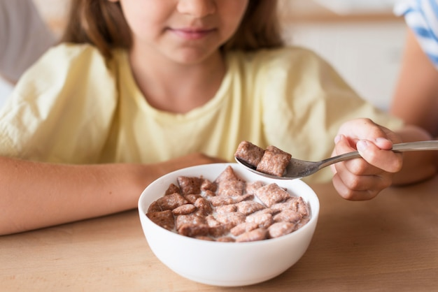 Ragazza del primo piano che mangia latte e cereali