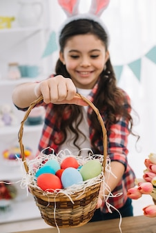Close-up of a girl giving colorful easter eggs basket