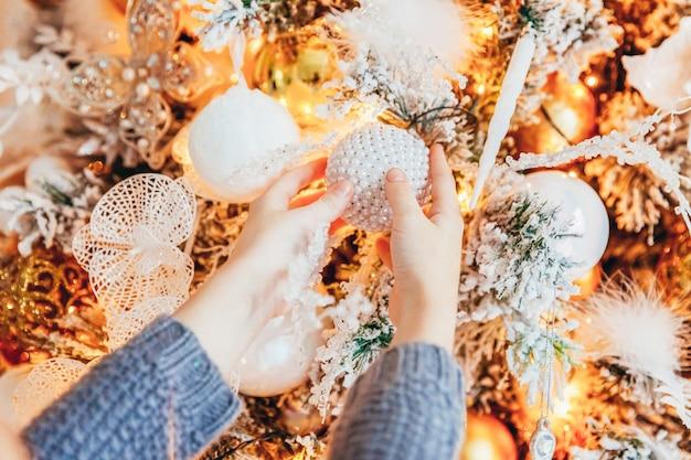 Крупным планом девушки руки украшения елки дома