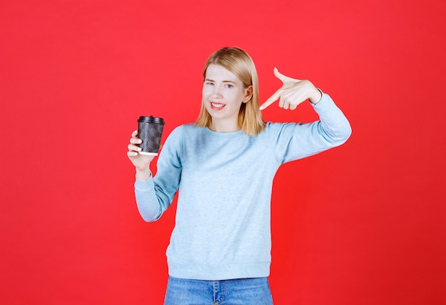 찻잔 커피를 들고 빨간색에 poiting 소녀를 닫습니다