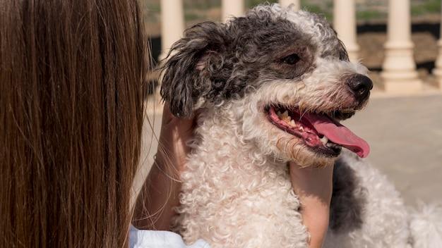 Крупным планом девушка держит очаровательную собаку