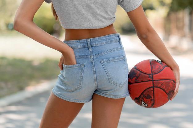 Крупным планом девушка держит мяч
