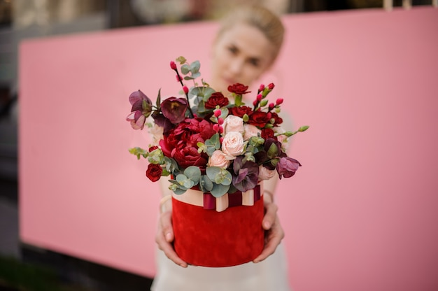 Close-up of girl holding bouquet in hat box