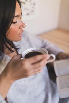 Primo piano di un libro di lettura della tazza di caffè della tenuta della ragazza