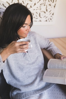 Close-up of a girl holding cup of coffee reading book