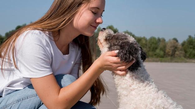 Крупным планом девушка держит голову собаки