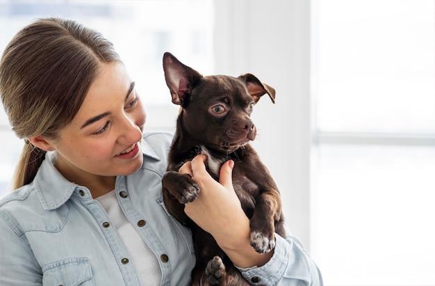 Крупным планом девушка держит собаку