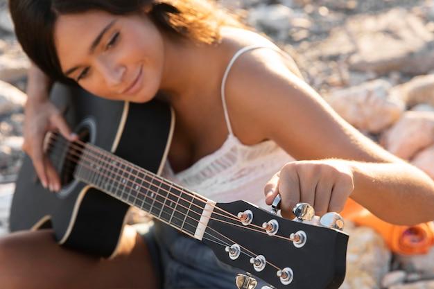 Крупным планом девушка держит гитару