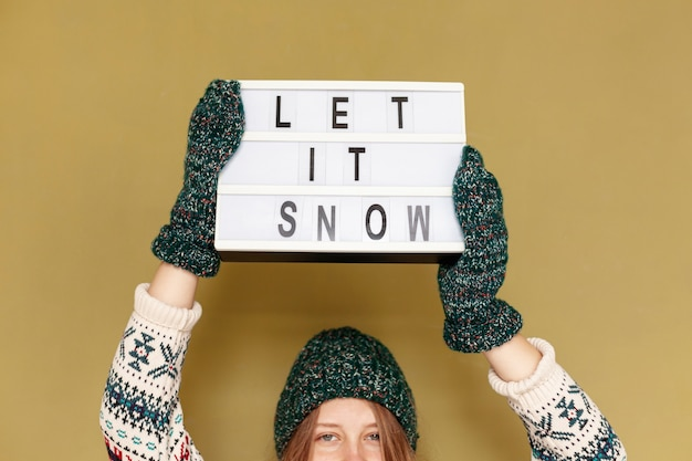 Close-up girl holding let it snow sign