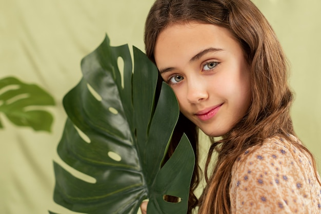 Close up girl holding monstera leaf