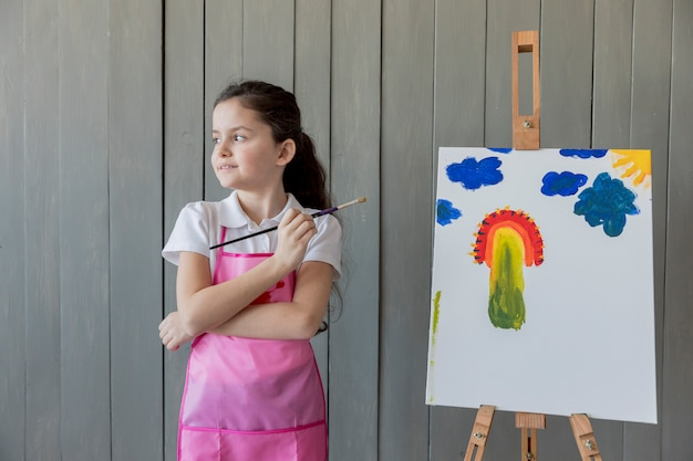 Close-up of a girl holding paint brush in hand standing near the easel looking away