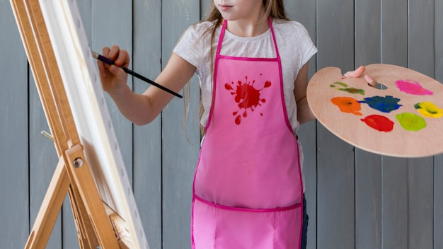 Close-up of a girl holding palette in hand painting on the easel with paint brush