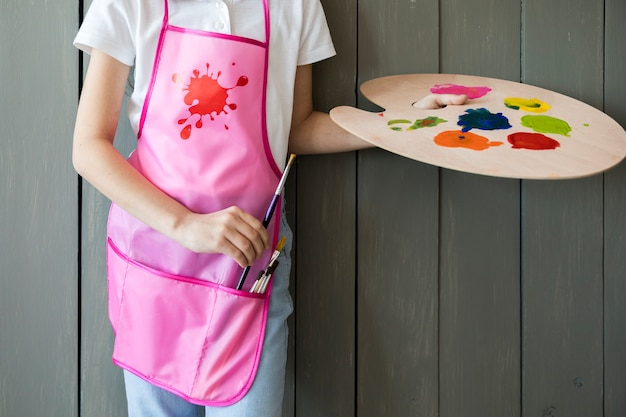 Close-up of a girl holding palette in hand removing the paint brush from pink apron standing against grey wooden wall