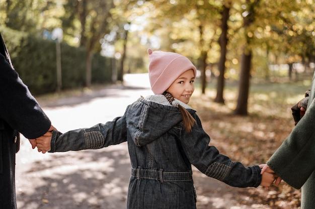 Девушка крупным планом, взявшись за руки родителей