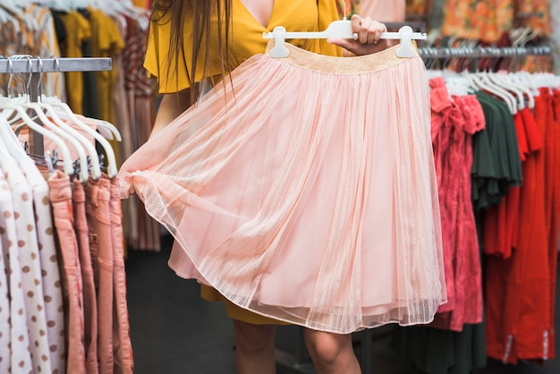 Close-up girl holding a pink skirt