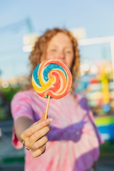Close-up girl holding up lollipop
