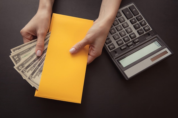 Close-up. the girl is holding a yellow envelope with money on a dark leather background, on the table is a calculator.