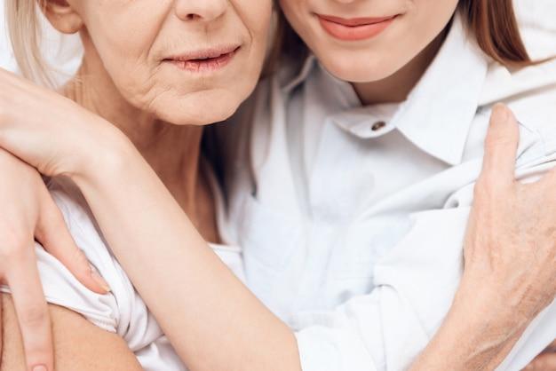 Close up girl is nursing elderly woman hugging at clinic