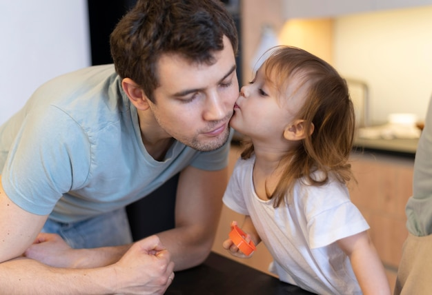 Ragazza del primo piano che bacia padre sulla guancia